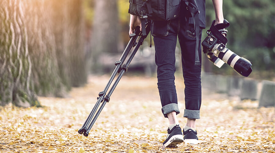 photographer carrying tripod and camera
