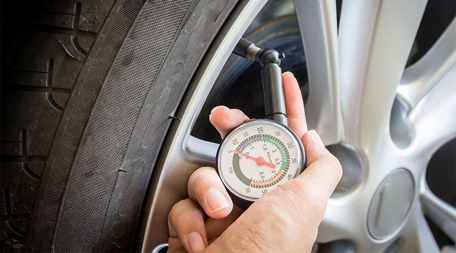 checking tyre pressure of car